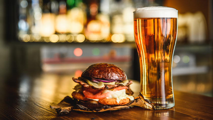Hamburger and light beer at the bar on wooden background