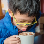 young-asian-boy-blowing-hot-chocolate-drink-in-cafe