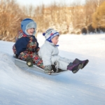 two-joyful-child-sledding-down-the-hills-in-a-winter-day