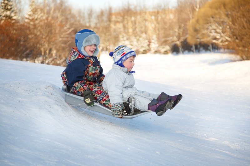 two kids sledding