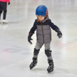adorable-little-boy-in-winter-clothes-with-protections-skating-on-ice-rink