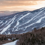 a-fleet-of-snowcats-grooming-spruce-peak-at-dusk-with-mt-mansfield-in-the-background-stowe-vermont-usa